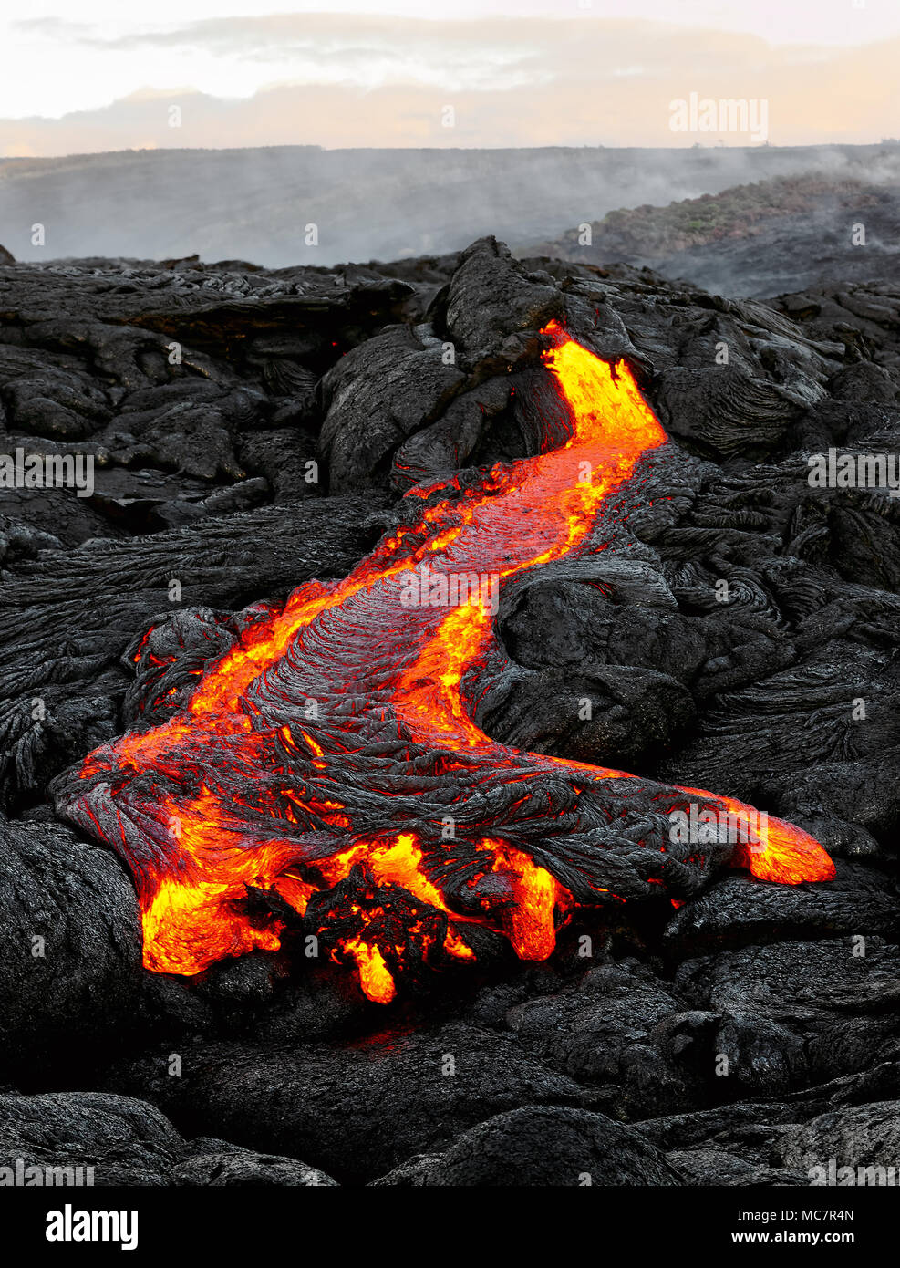 A lava flow emerges from an earth column and flows in a black volcanic landscape, in the sky shows the first daylight - Location: Hawaii, Big Island,  - Stock Image
