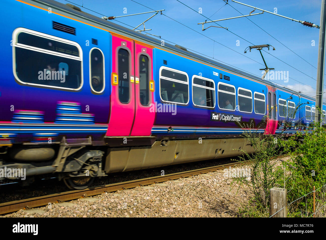 First Capital Connect Class 365 railway train travelling at speed. Carriage with passengers. Electric multiple unit emu overhead wires and pantograph - Stock Image