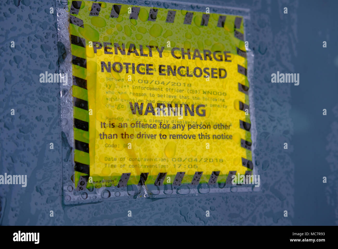 Penalty Charge for illegal parking. Parking ticket stuck on windscreen of a car - Stock Image