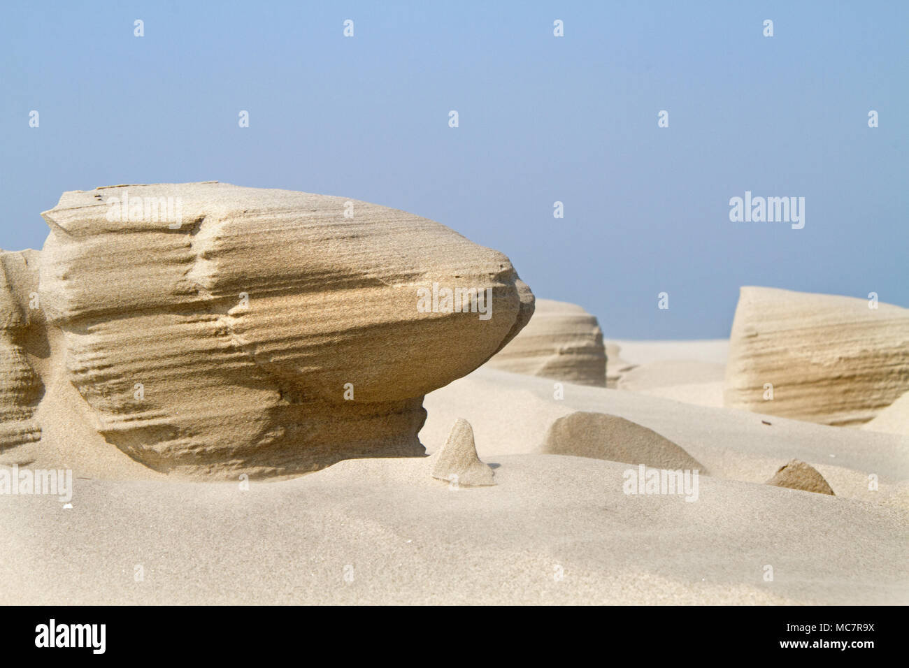 Wind erosion forms strange sculptures in the sand of a beach - Stock Image