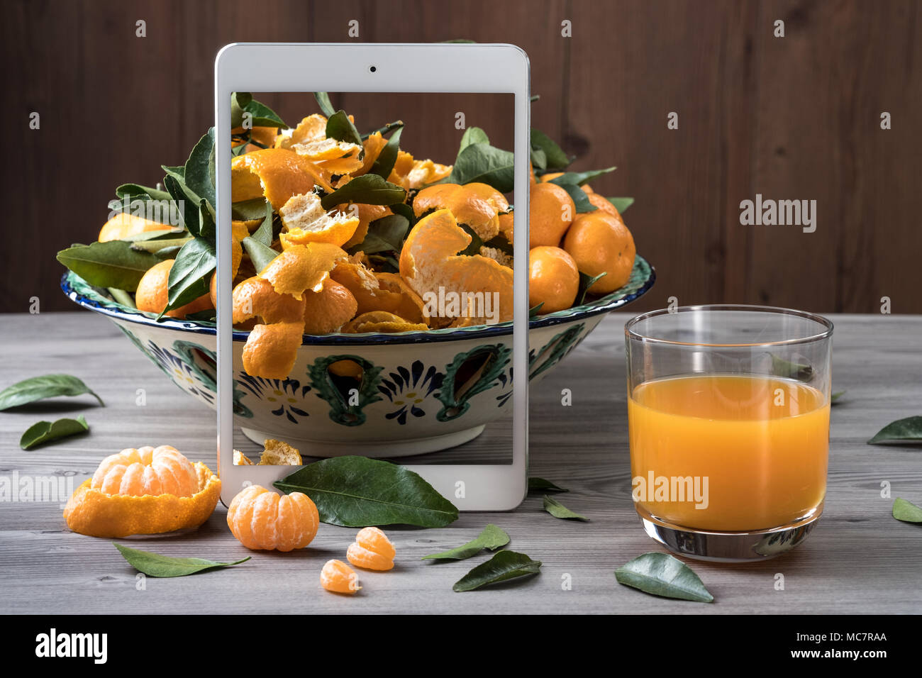 White mobile tablet standing in front of ceramic dish filled fresh tangerines on gray wooden table. Pop up visual effect. Creative food composition. - Stock Image