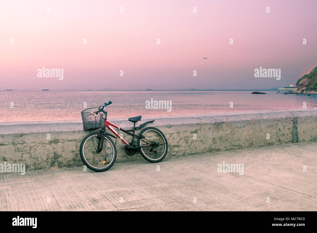 Lonely bicycle with metal basket standing on concrete pier. Seascape background with fishing boats on horizon line. Toned image. - Stock Image