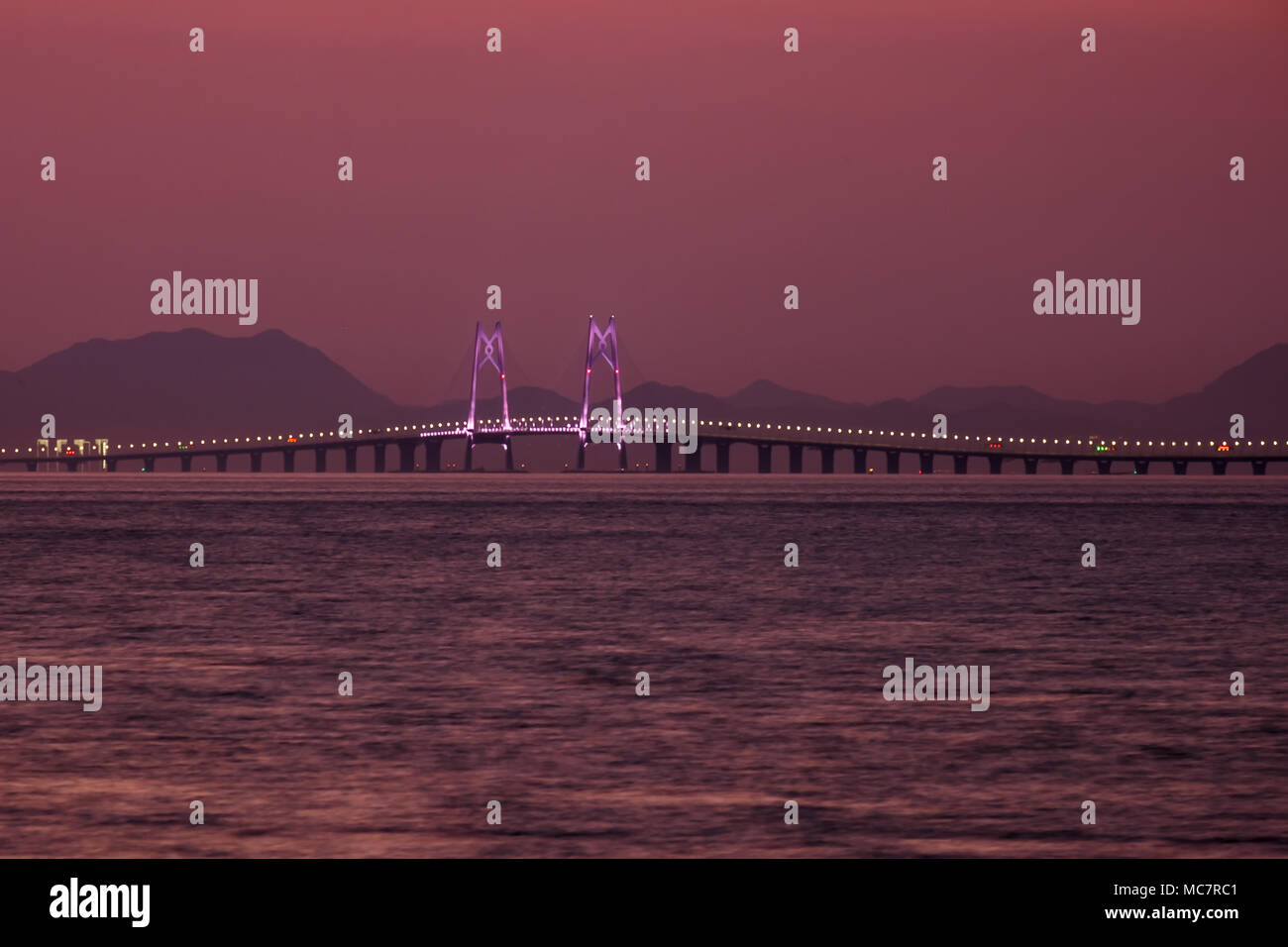 Hong Kong - Zhuhai - Macau bridge is the longest sea link in the world with underwater tunnel. Hong Kong part of bridge. Sunset sky on background. - Stock Image