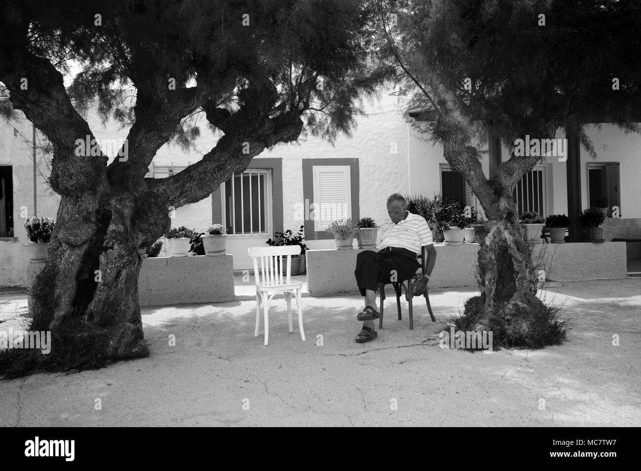 Man having a snooze in the shade of a two trees, Rhodes, Greece - Stock Image