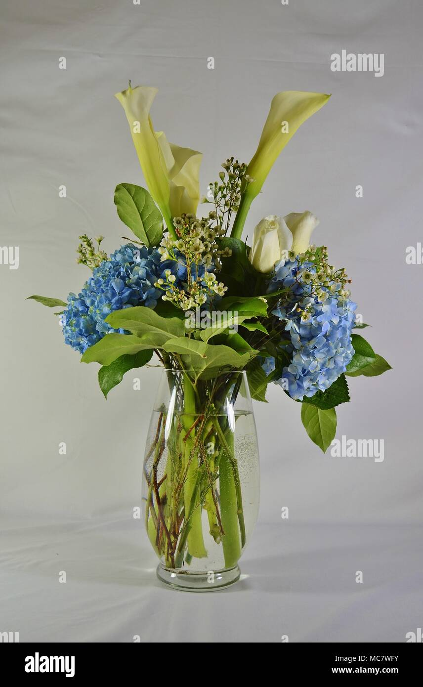 Beautiful Tall Glass Vase Filled With Pretty Flowers And Fresh Green Leaves Stock Photo Alamy
