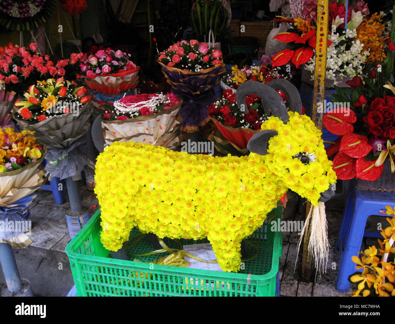 Goat composed of yellow apricot flowers in Saigon Chinese market representing the Year of the Goat - Stock Image