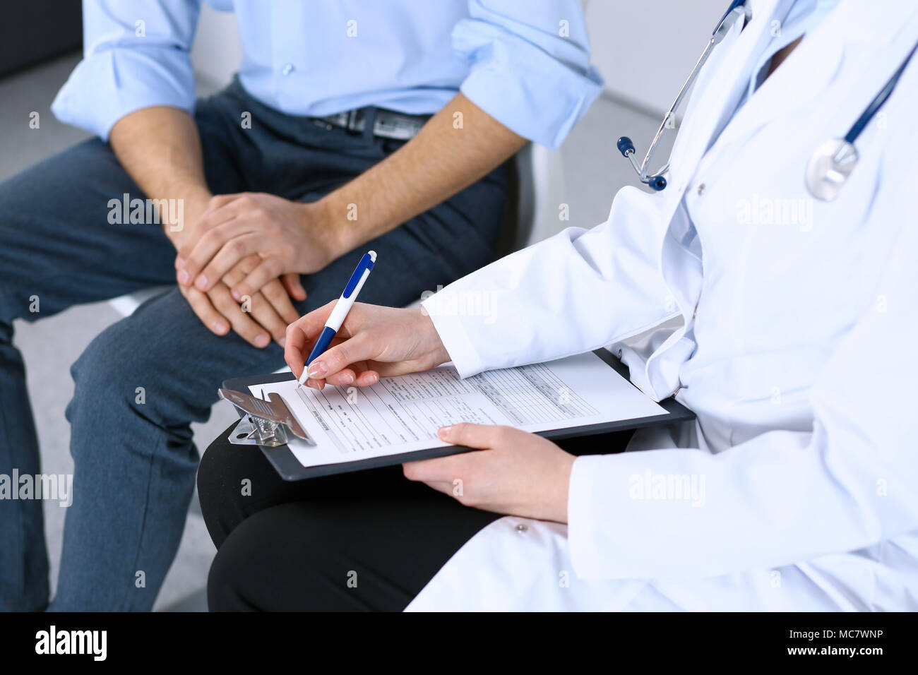 Female doctor holding application form while consulting man patient female doctor holding application form while consulting man patient in hospital medicine and healthcare concept thecheapjerseys Choice Image