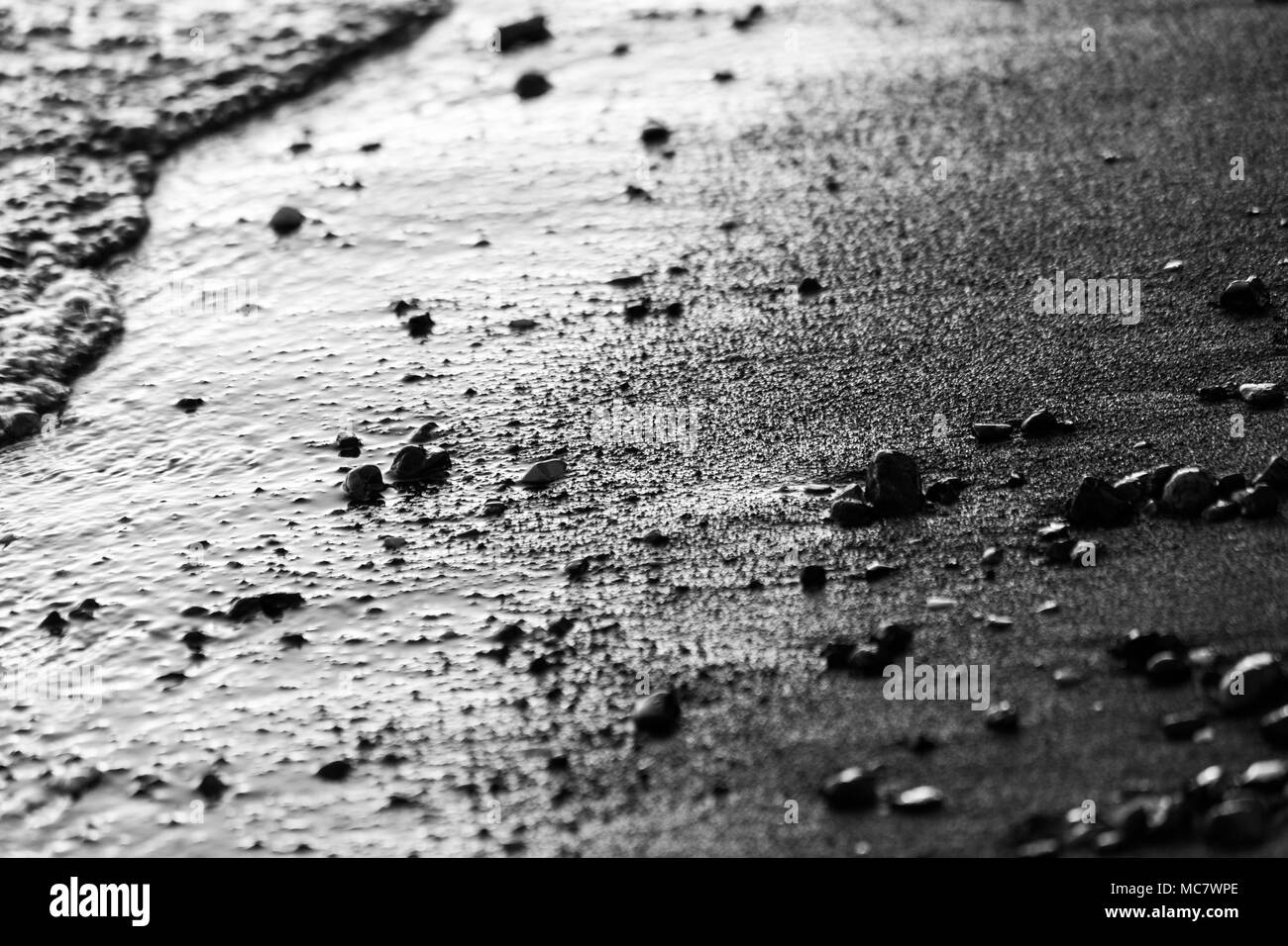 A close view of water on a lake shore at sunset, with details of sands and little round stones - Stock Image