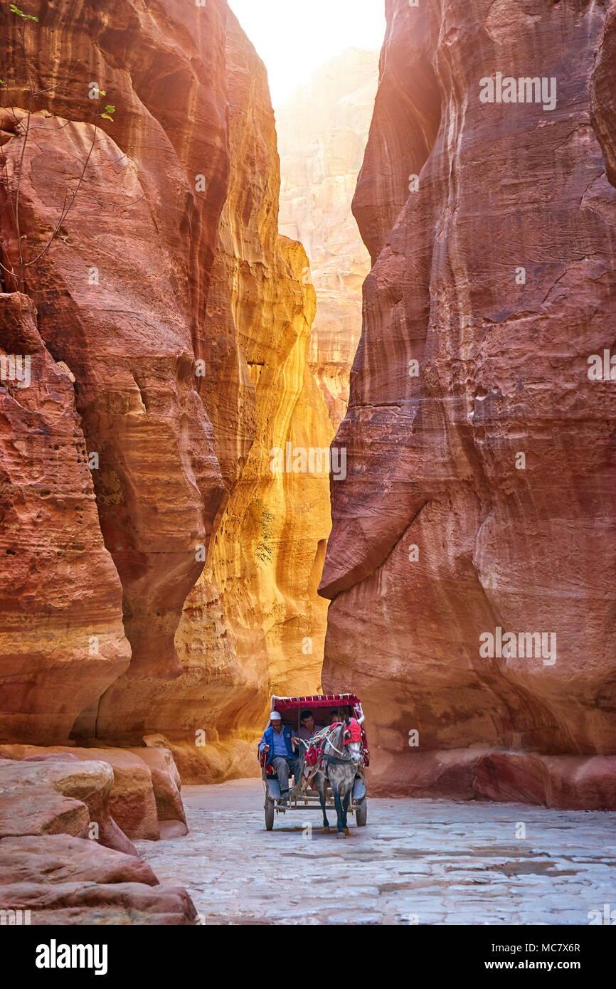 Horse carriage riding through the Siq Canyon to the Treasury, Petra, Jordan - Stock Image