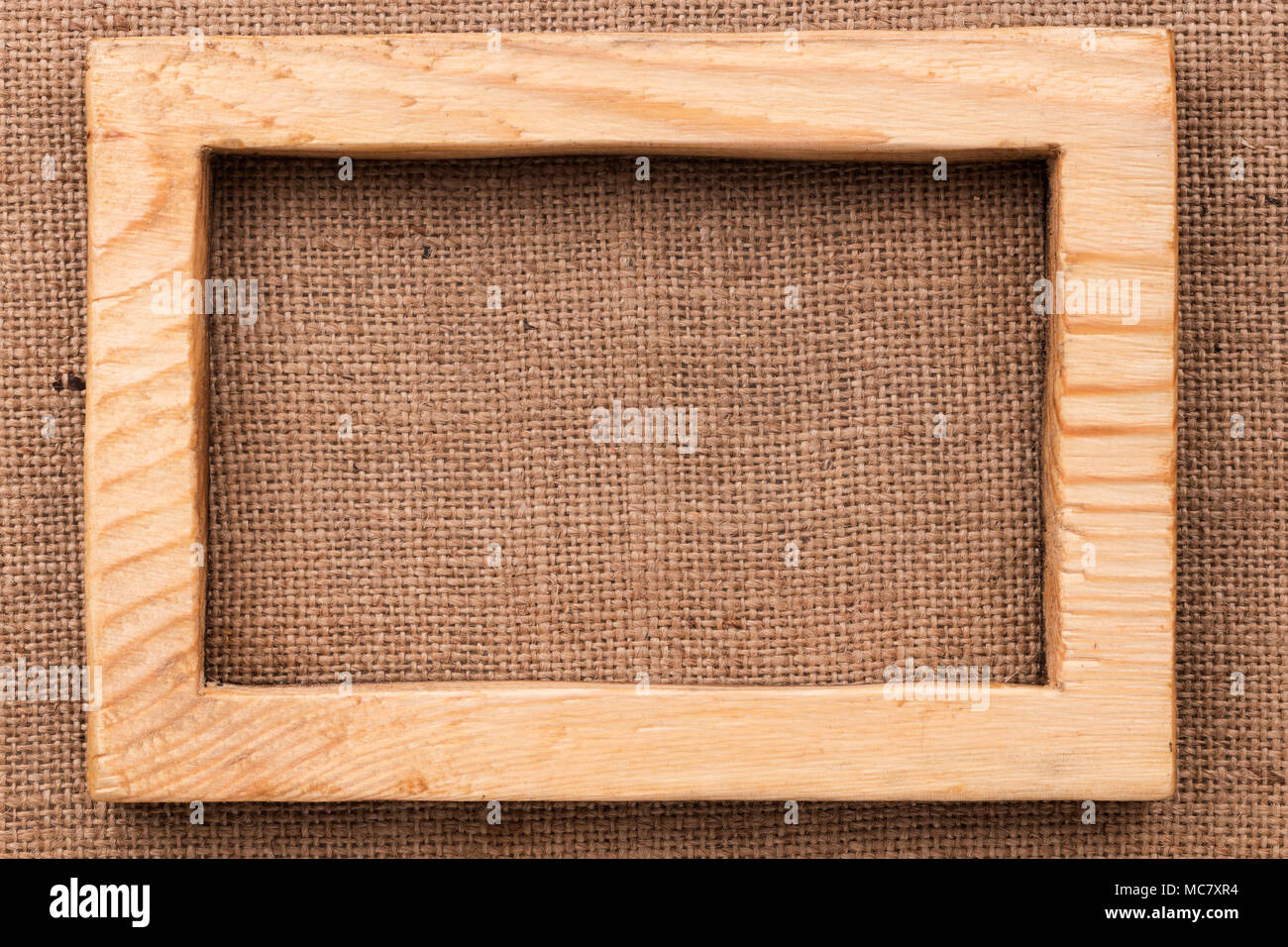 Vintage frame made of light wood lying on burlap. With space for ...