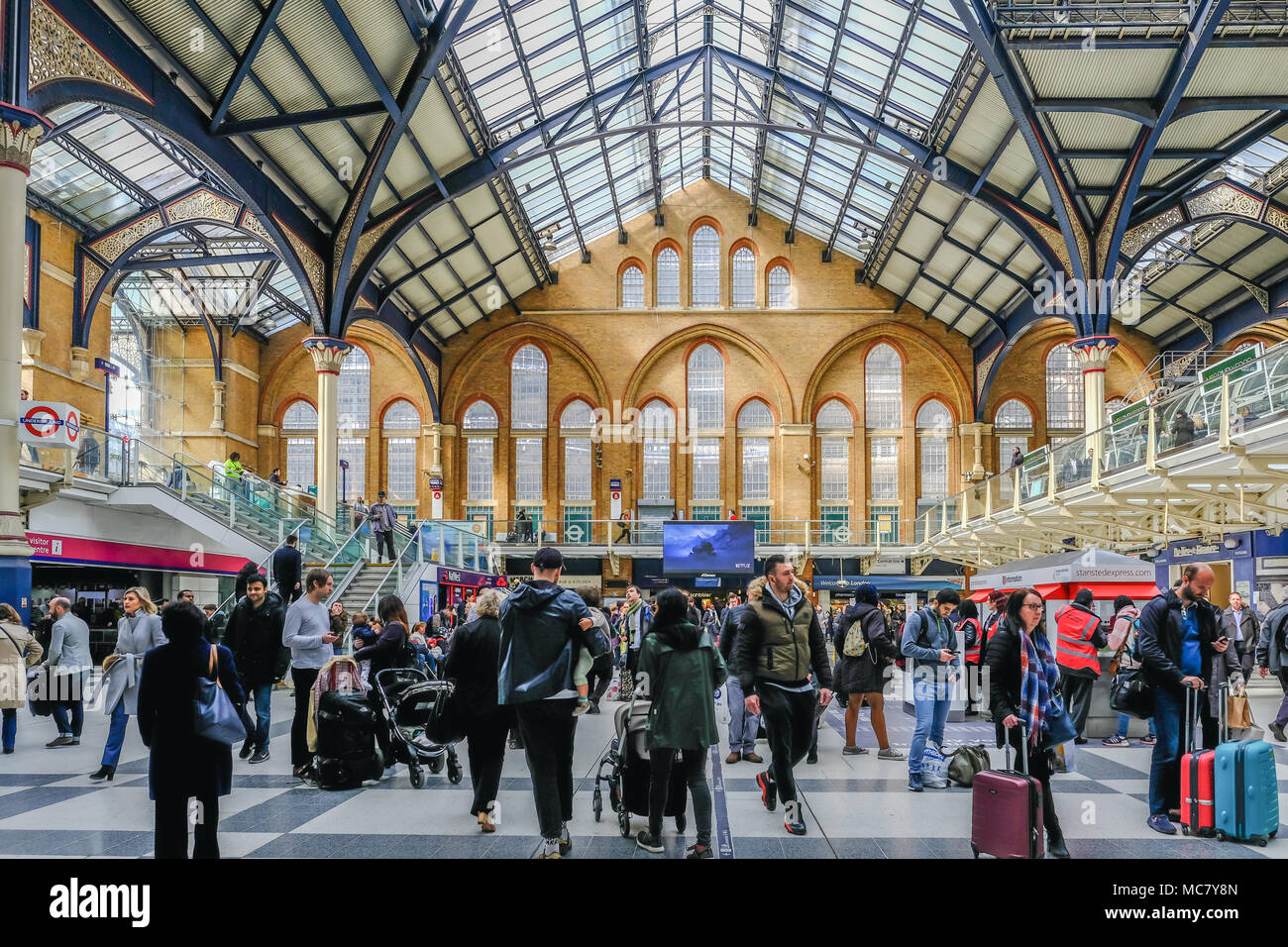 Liverpool Street, London, UK - April 6, 2018: wide angle shot of a busy mainline station with lots of passengers. Well lit view of the architecture. - Stock Image