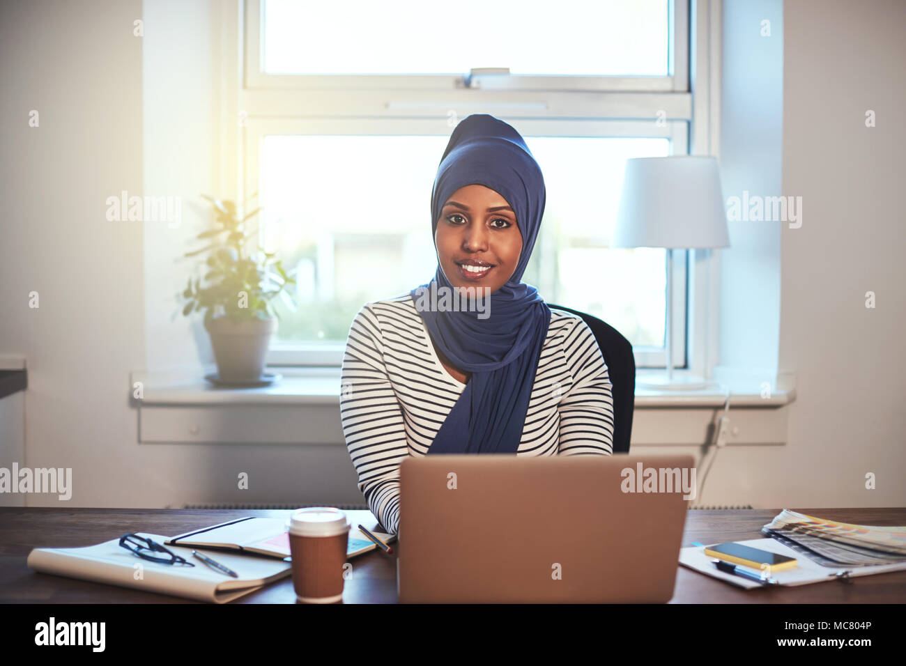 Young Arabic female entrepreneur wearing a hijab smiling confidently while working on a laptop in her home office Stock Photo