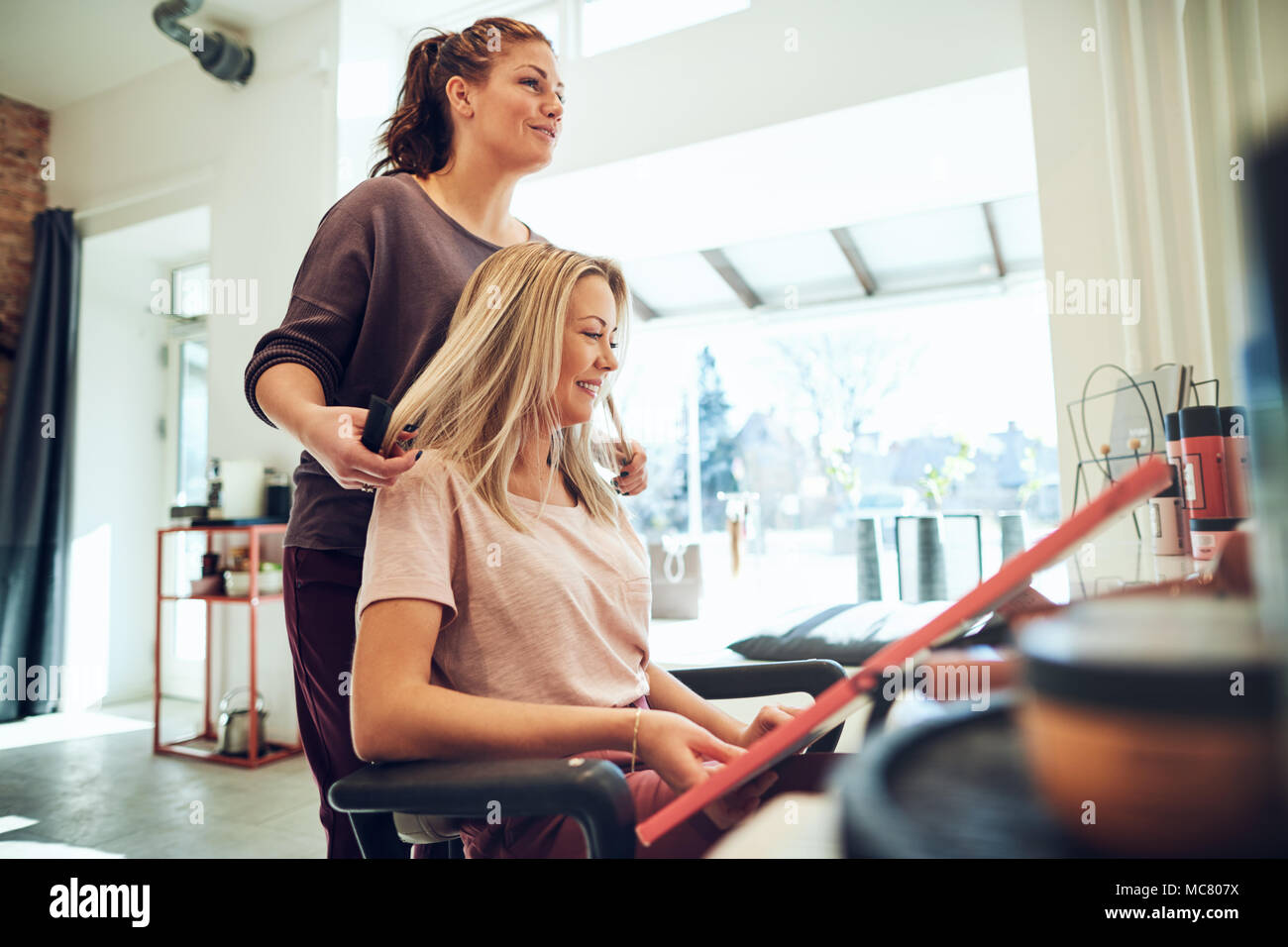 Young blonde woman choosing a new hair color from samples in a book ...