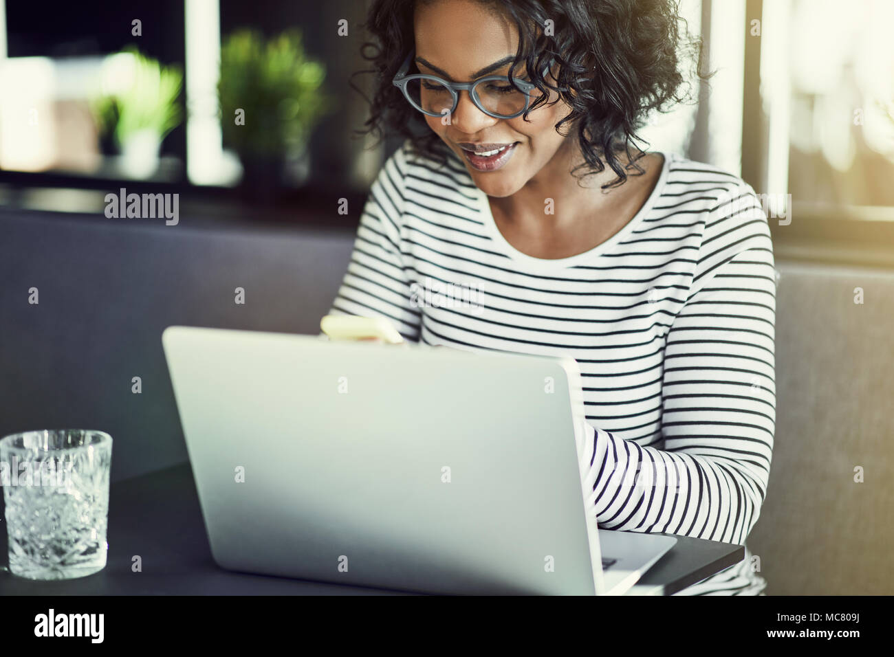 Smiling young African woman wearing glasses sitting at a table sending a text message on her cellphone and working online with a laptop - Stock Image