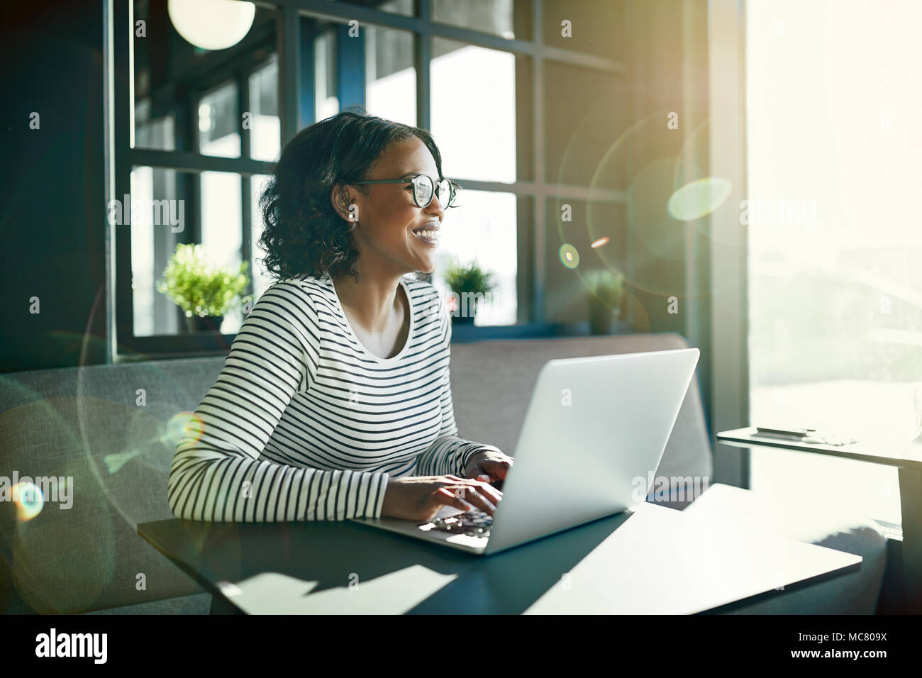 Smiling young African woman wearing glasses looking out of a window while sitting at a table working online with a laptop - Stock Image