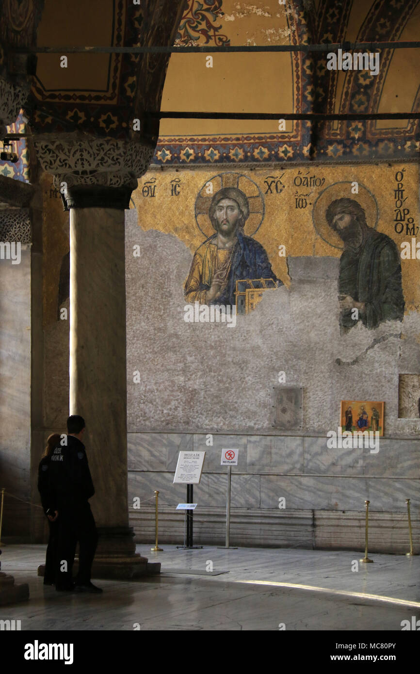 Tourists in front of parts of the Deësis mosaic, ancient Christian art showing Christ and John the Baptist, on the upper gallery inside Hagia Sophia Stock Photo