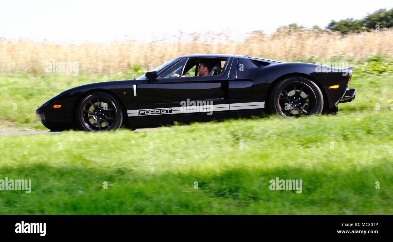 Low Angle Profile Side View Of A Black Ford Gt Supercar Hypercar Driving Fast