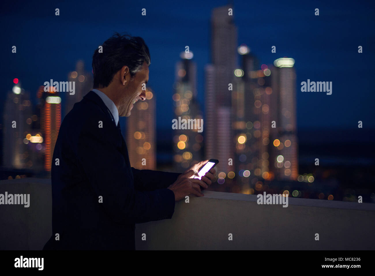 Businessman on high rise rooftop using mobile phone - Stock Image