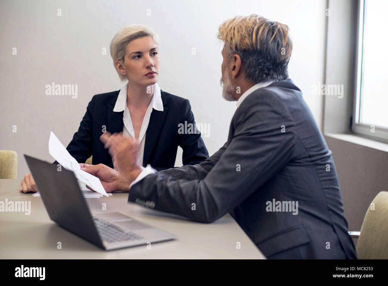Business woman talking with financial advisor - Stock Image