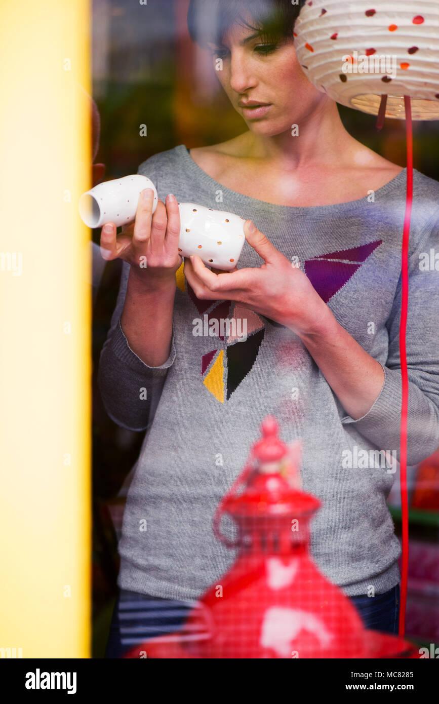 Woman shopping, viewed through window - Stock Image