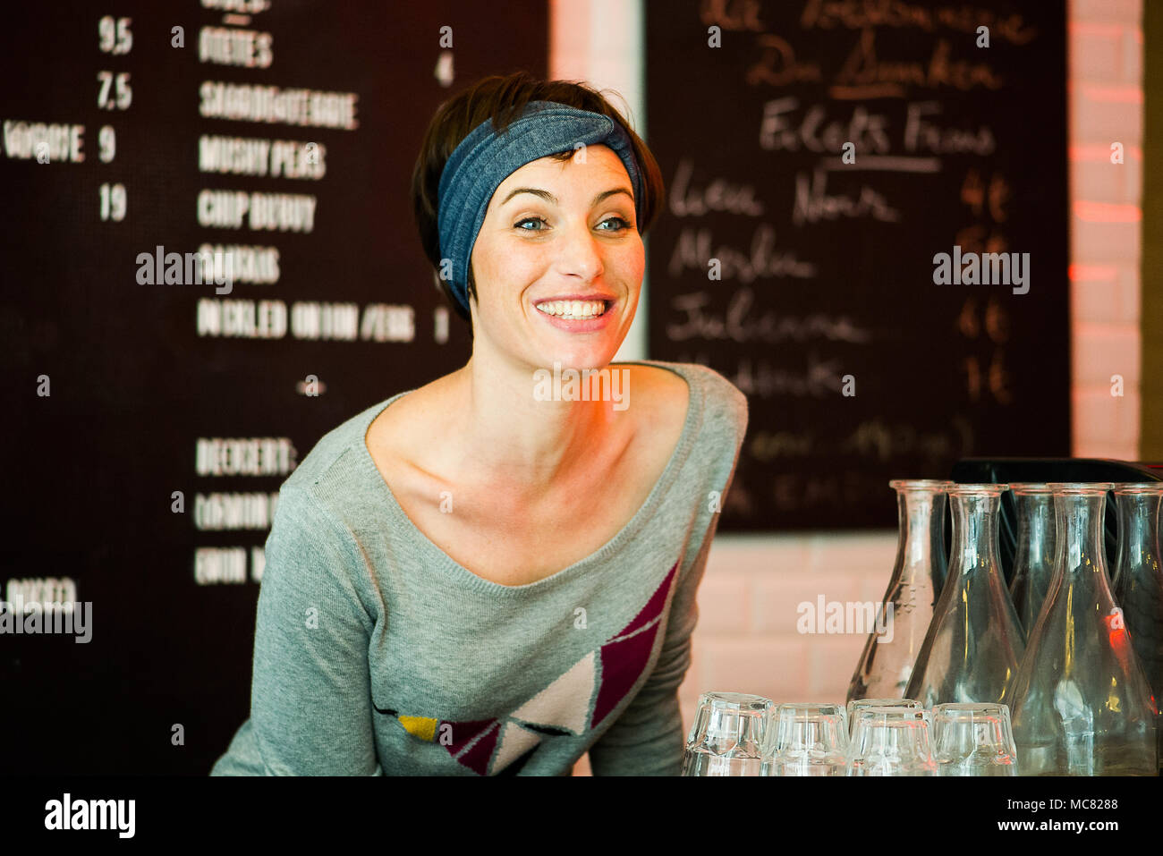 Woman smiling cheerfully in restaurant, portrait - Stock Image
