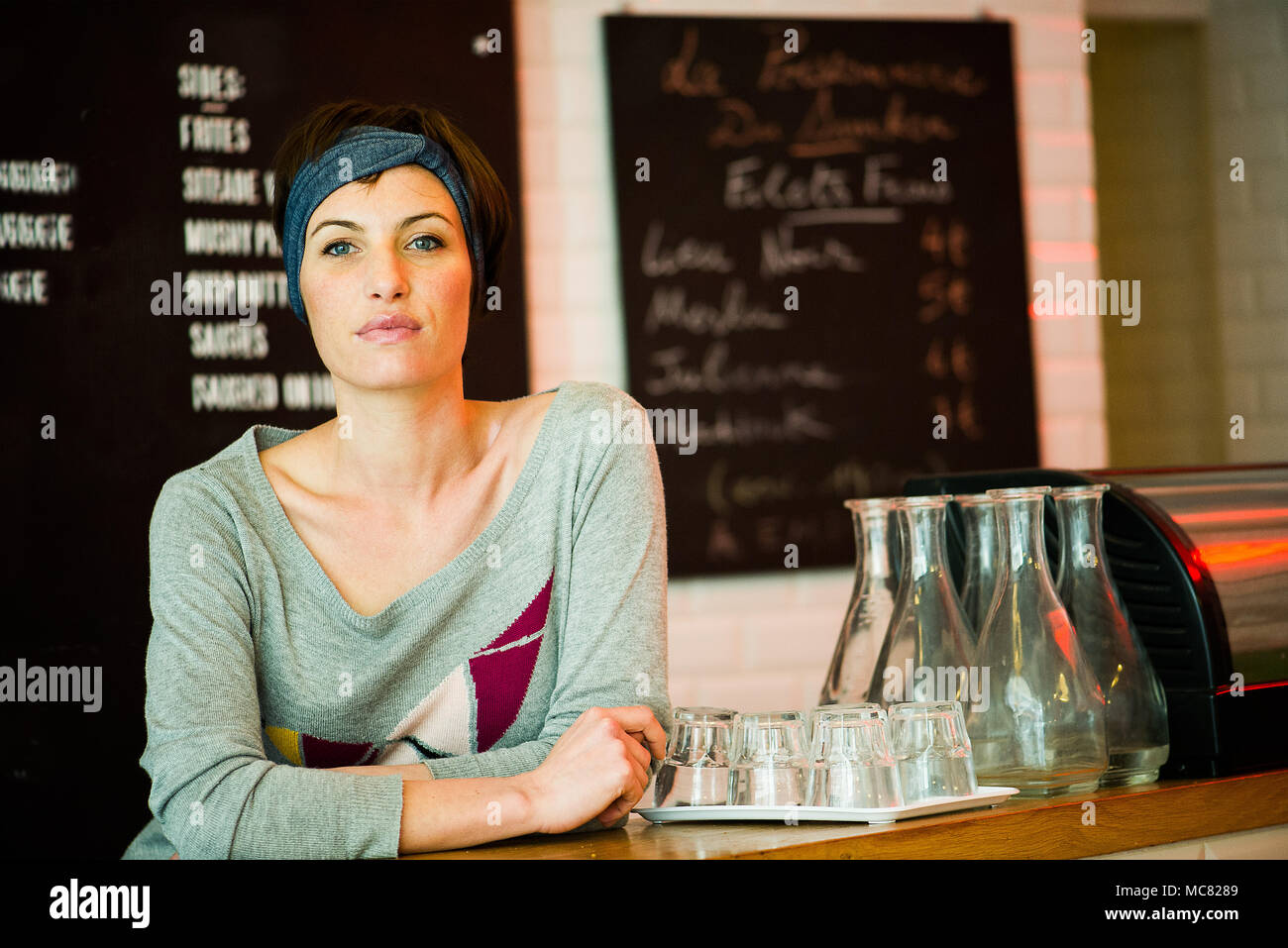 Waitress smiling in cafe, portrait - Stock Image