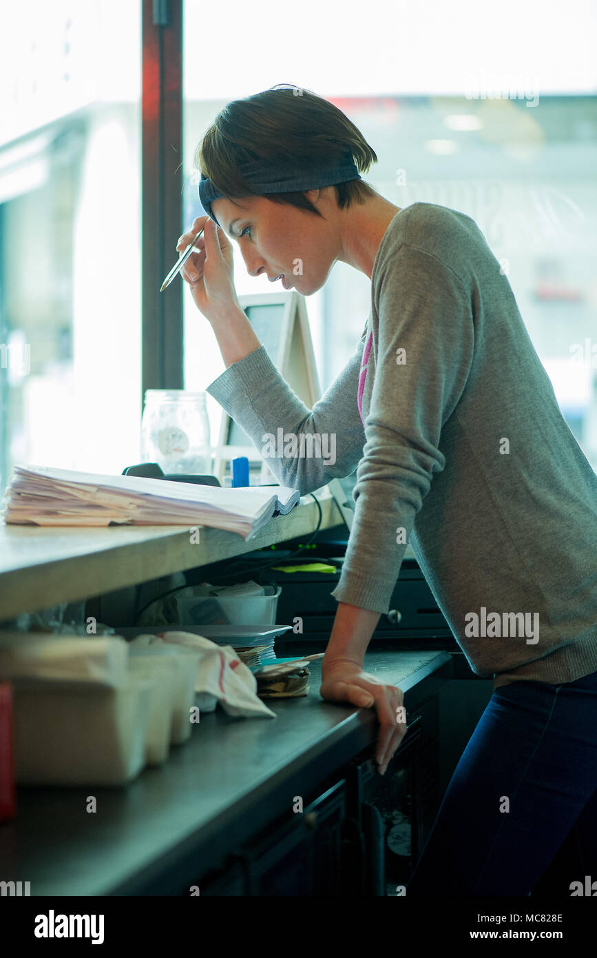 Cafe manager assessing finances - Stock Image
