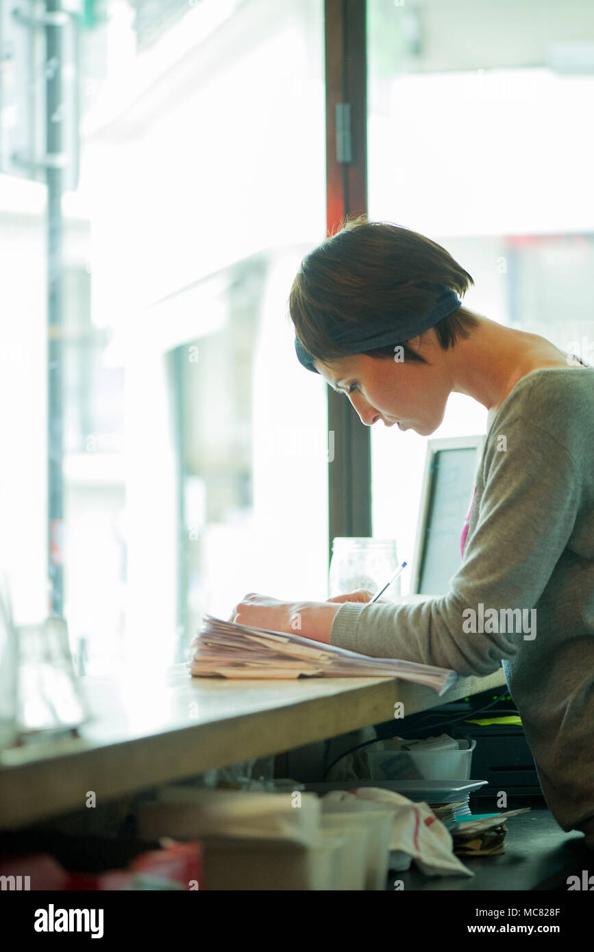 Cafe manager concentrating on work - Stock Image
