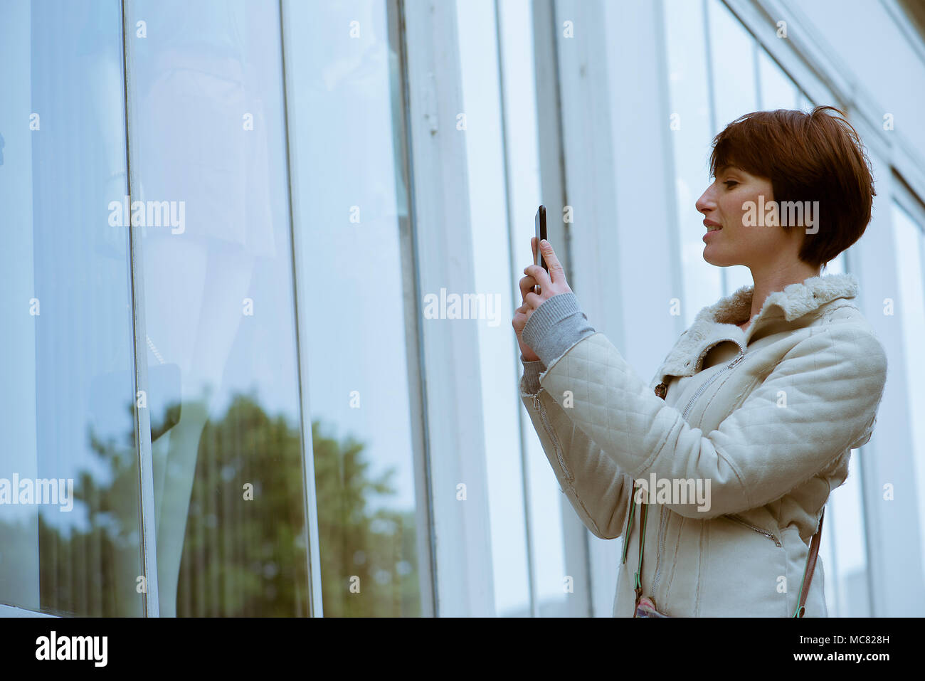 Woman photographing shop window with smartphone - Stock Image