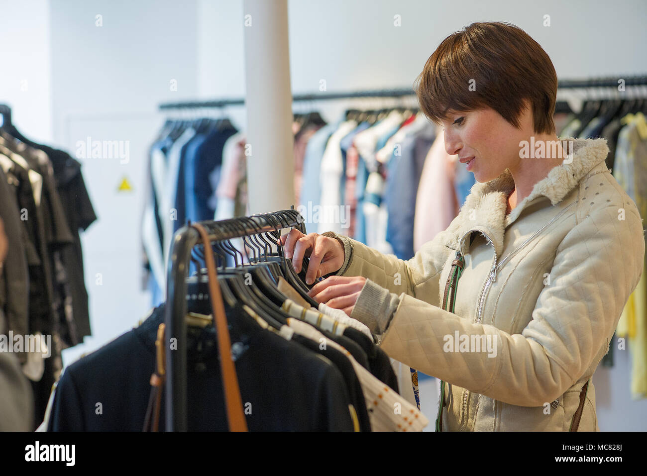 Woman shopping in clothing store - Stock Image