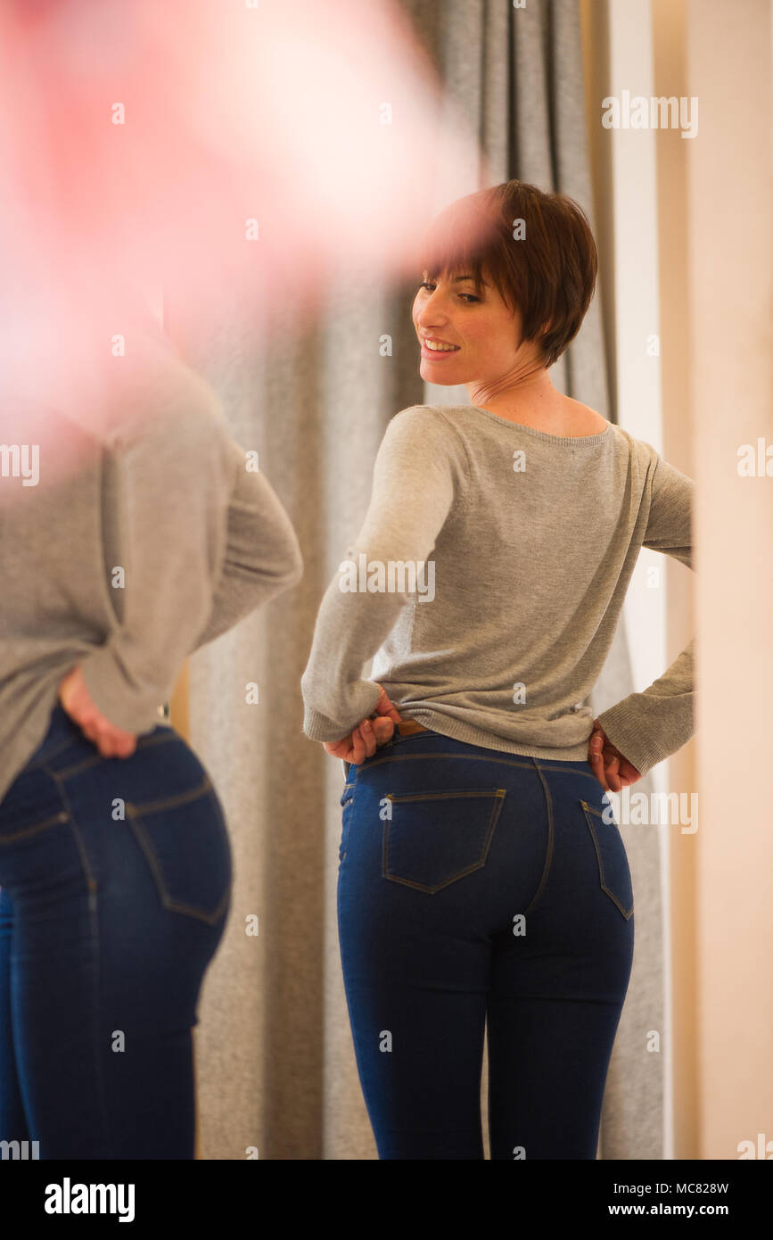 Woman trying on jeans in fitting room - Stock Image