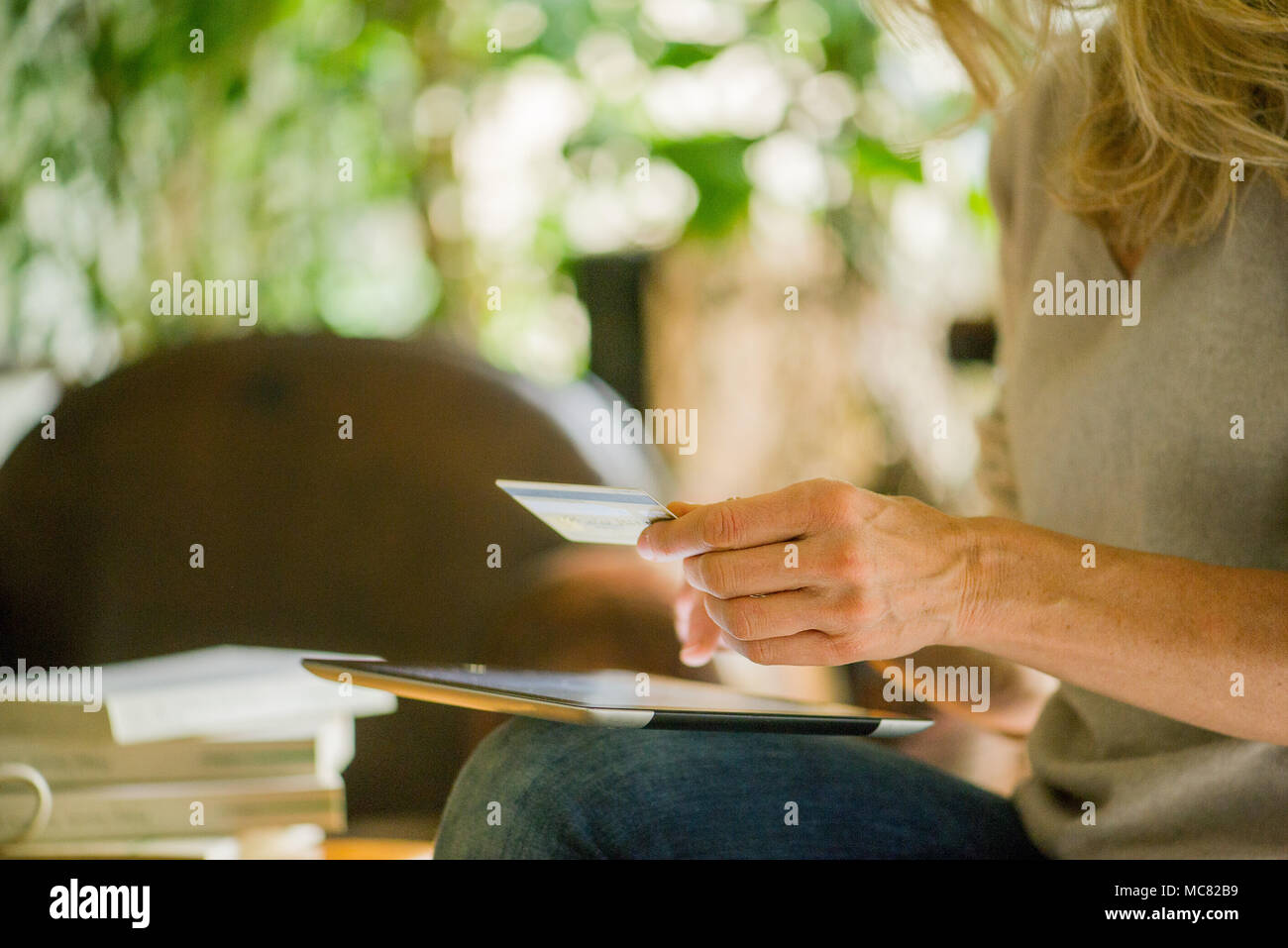 Woman using digital tablet and credit card, cropped - Stock Image