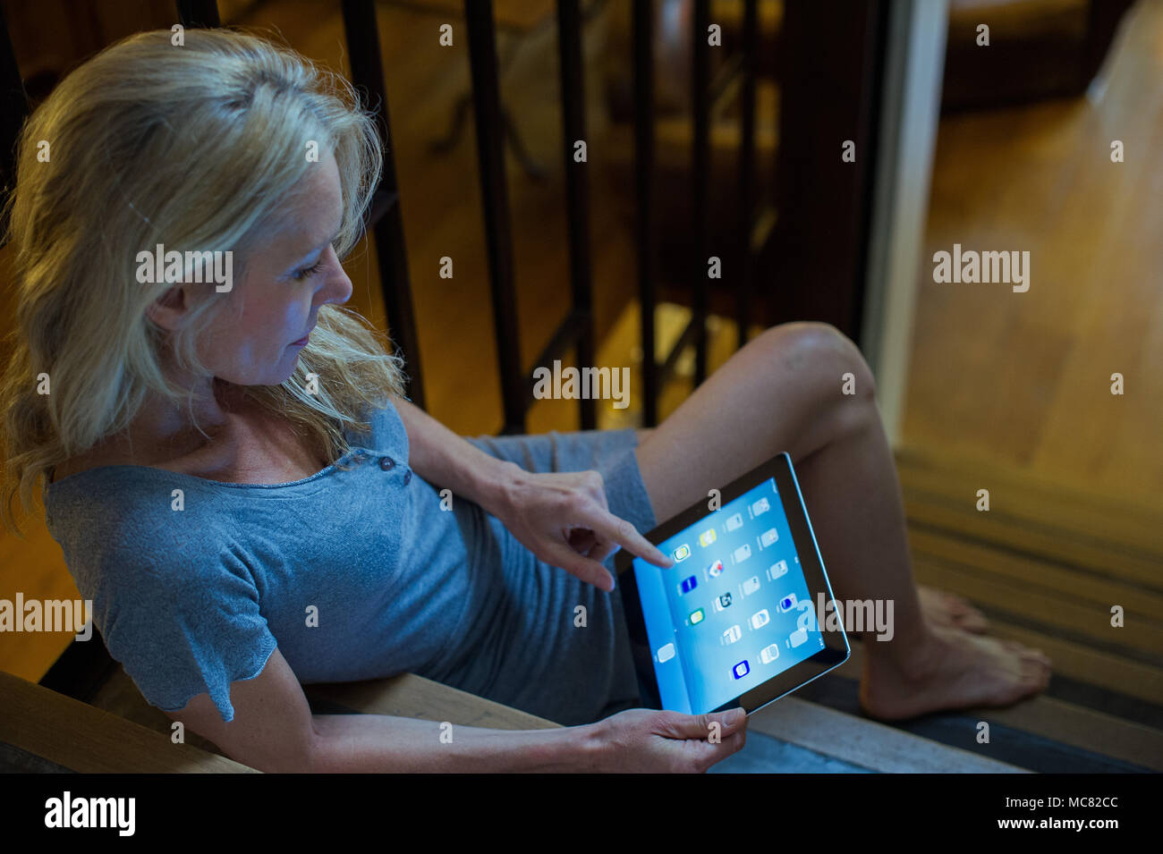 Mature woman sitting on stairs at home, using digital tablet - Stock Image