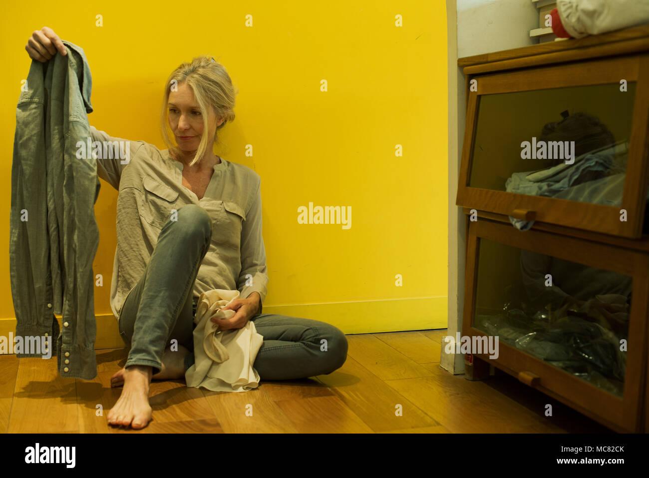 Mature woman sitting on bedroom floor, contemplating shirt - Stock Image