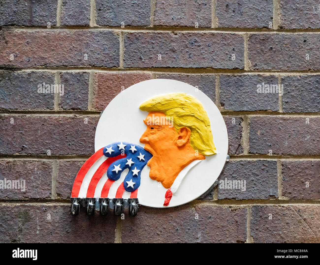 Wall plaque in  Bristol UK city centre alley showing Donald Trump putting America first spouting a Stars and Stripes flag with bombs on each stripe Stock Photo