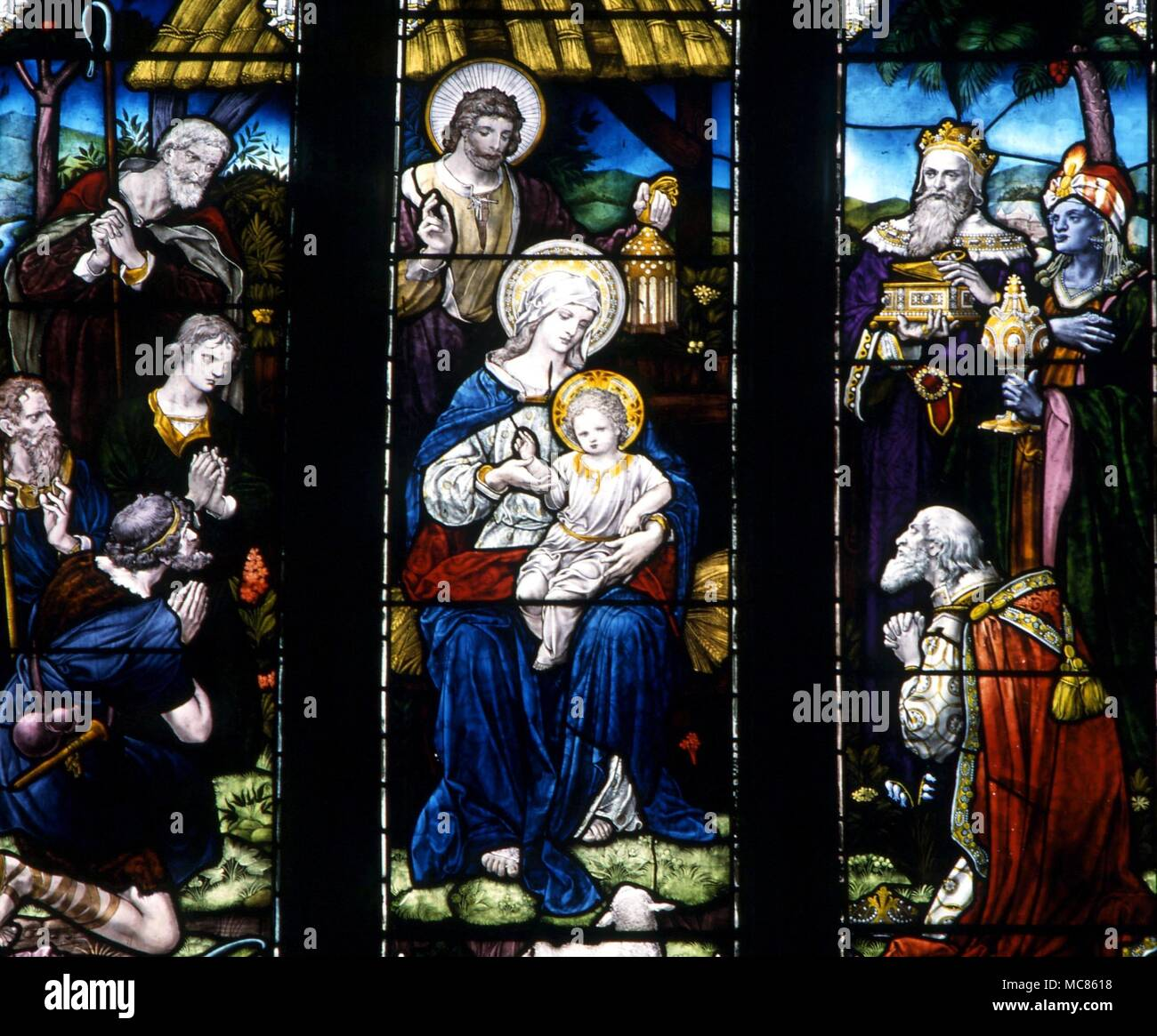 CHRISTIAN The Magi and the Shepherds attending the newlyborn Jesus with Mary and Joseph.  Stained glass in the church of St Mary, Godstone, Surrey - Stock Image