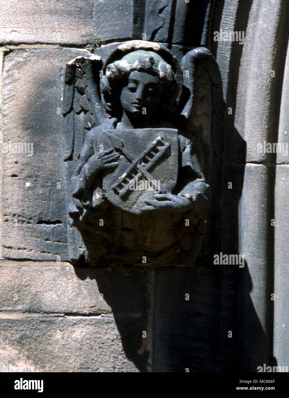 MYTHS Stone angel holding a heraldic device of the 'Arma Christi' - the instruments which caused Christ's suffering on the cross. On the porch of the parish church, Middlwich Stock Photo