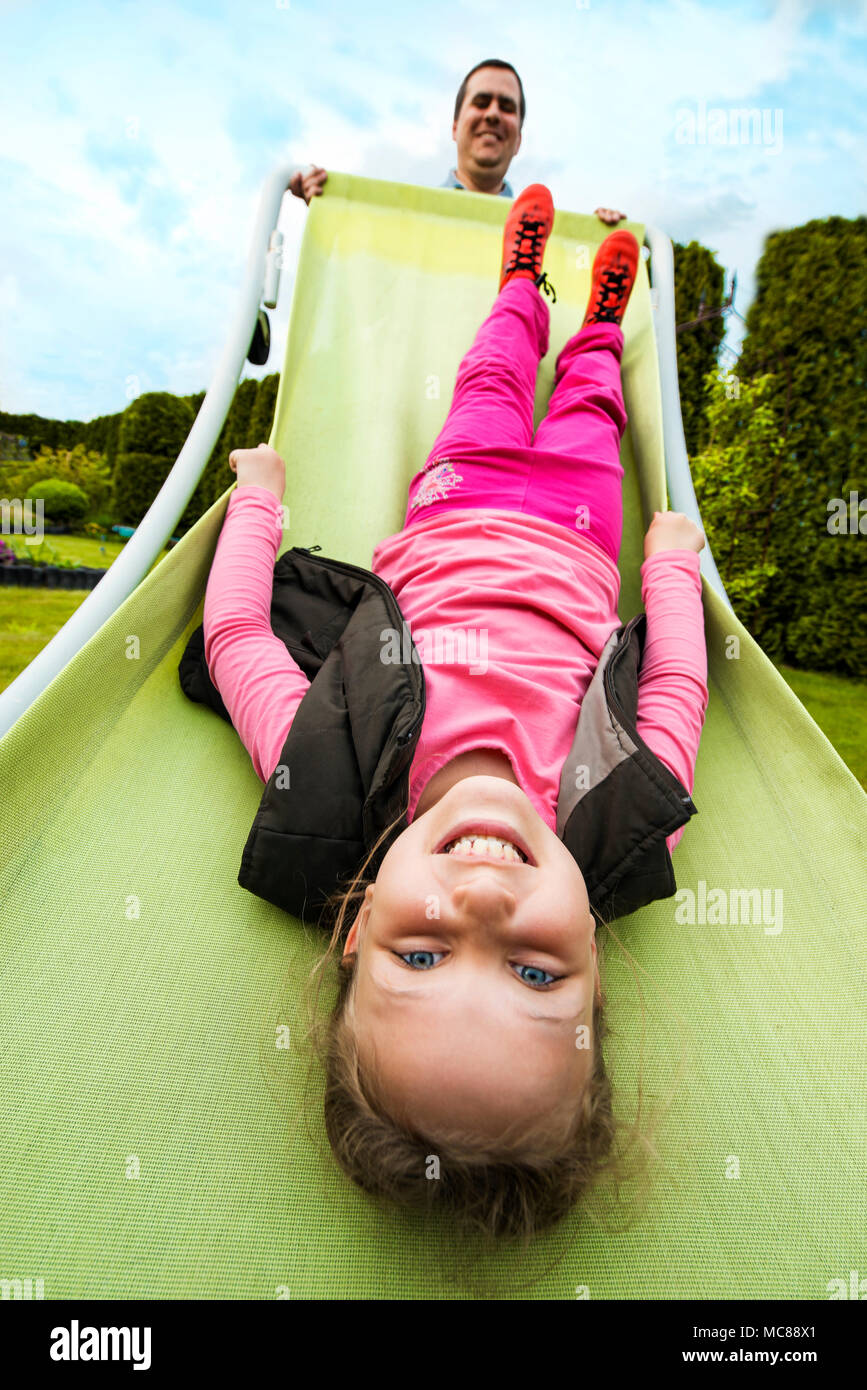 Young Girl Hanging Upside Down While Her Father Raising Hammock Chair Stock  Photo: 179662169   Alamy