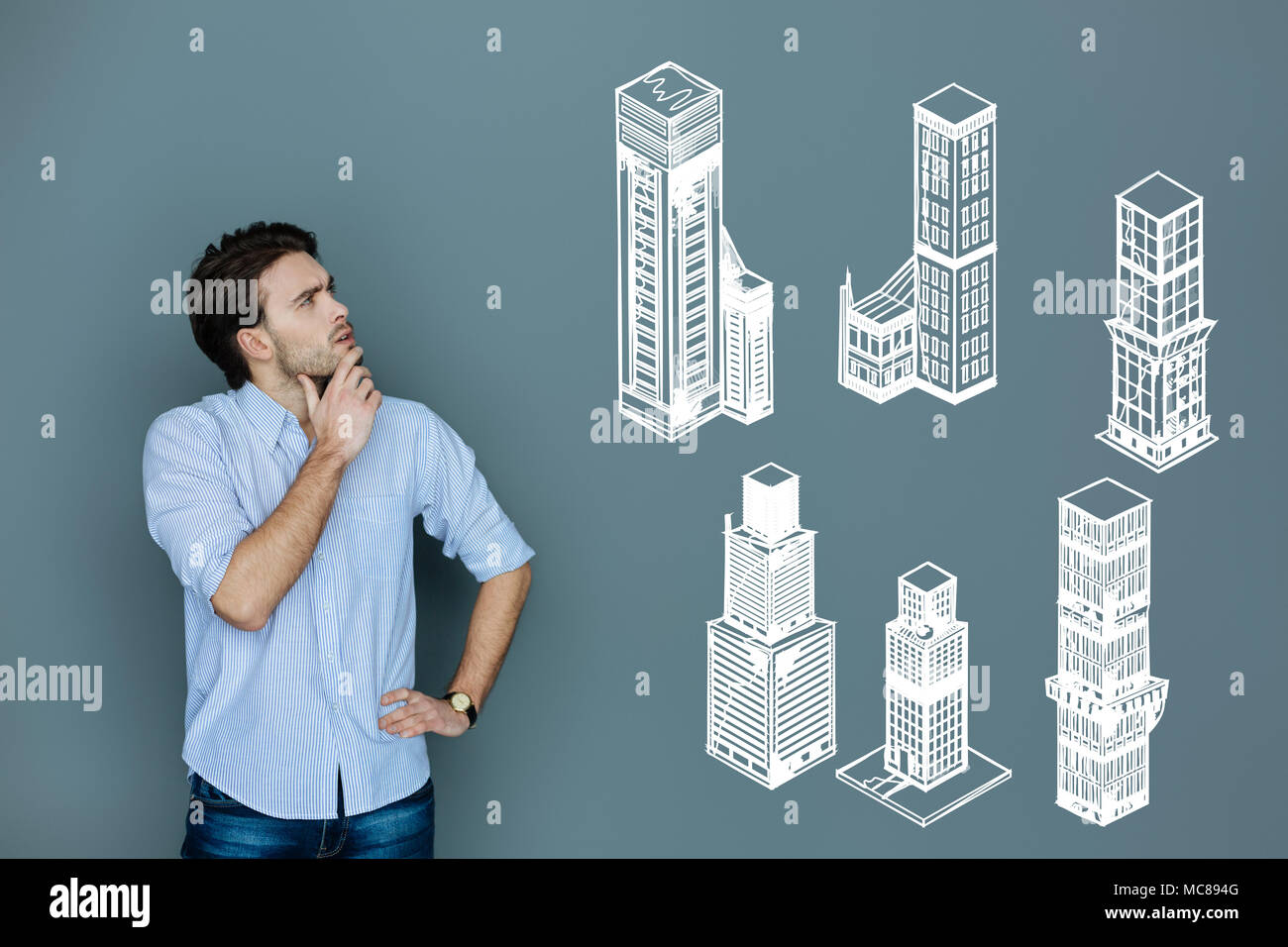 Qualified architect thinking while working at constructing skyscrapers - Stock Image