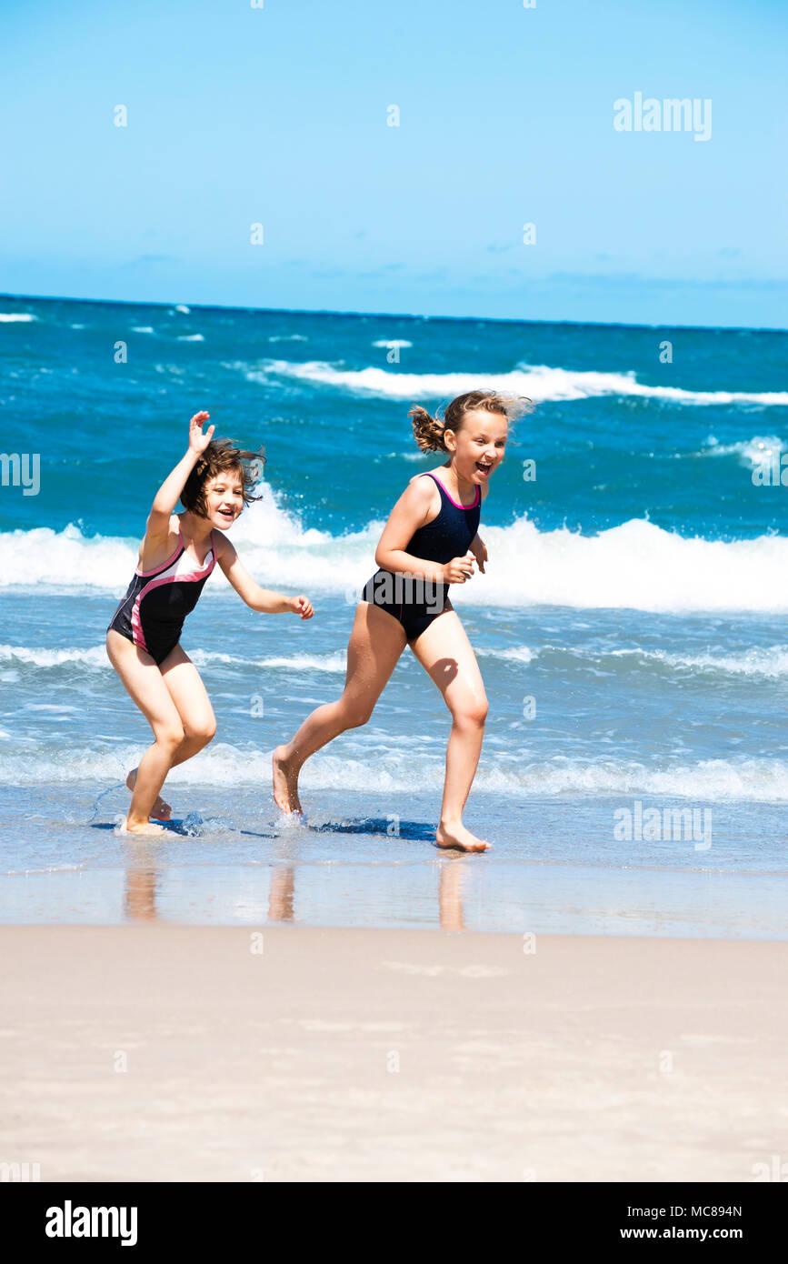 Two Girls Running Along Beach Smiling and Splashing Water. Stock Photo