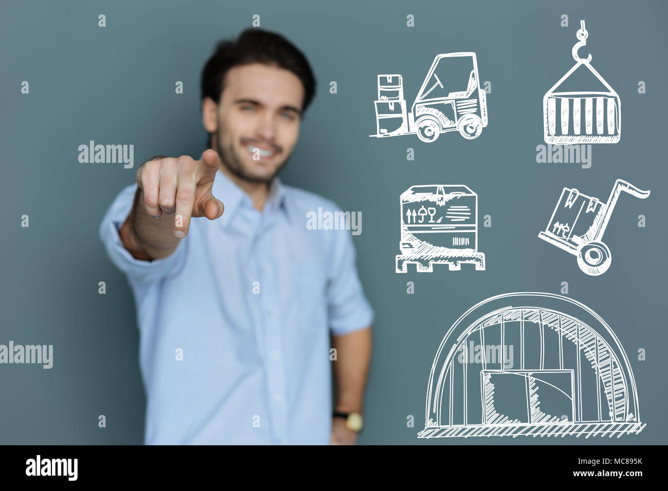 Cheerful laborer smiling and enjoying his hard work - Stock Image