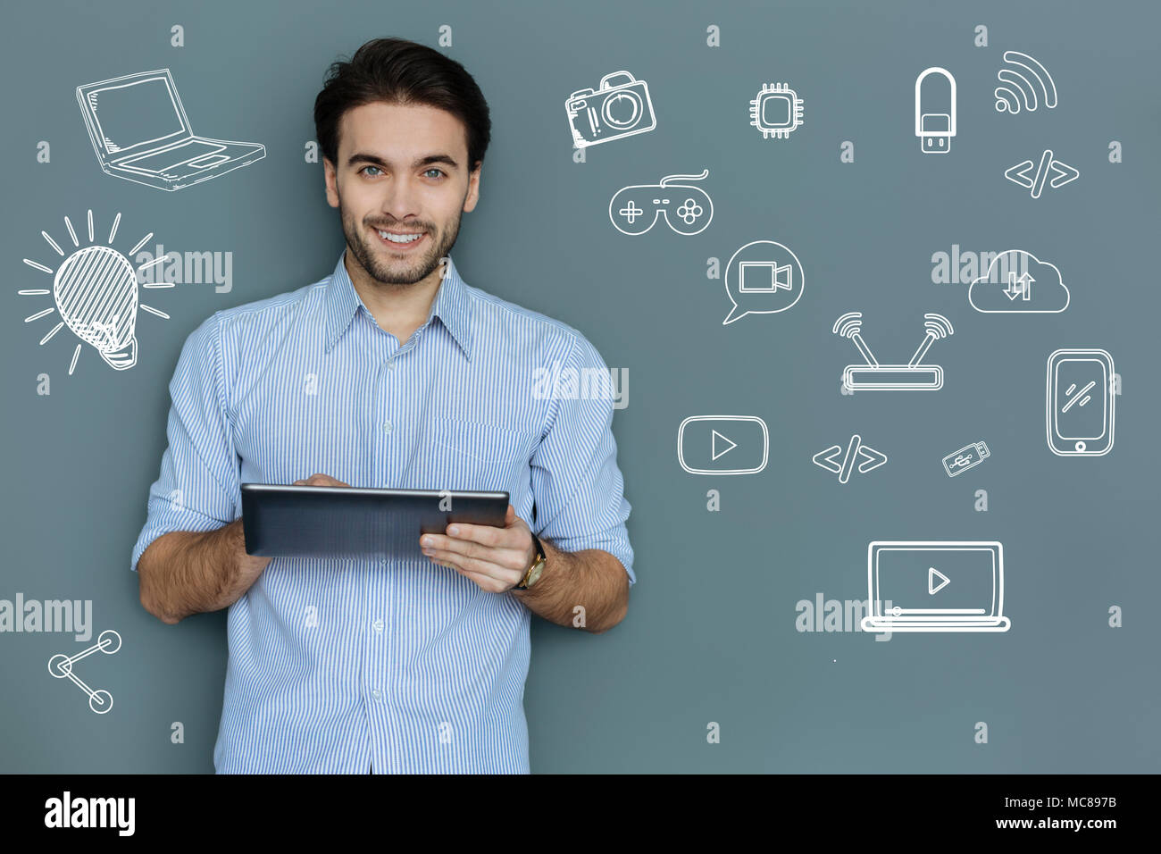 Experienced manager holding a modern tablet and smiling - Stock Image