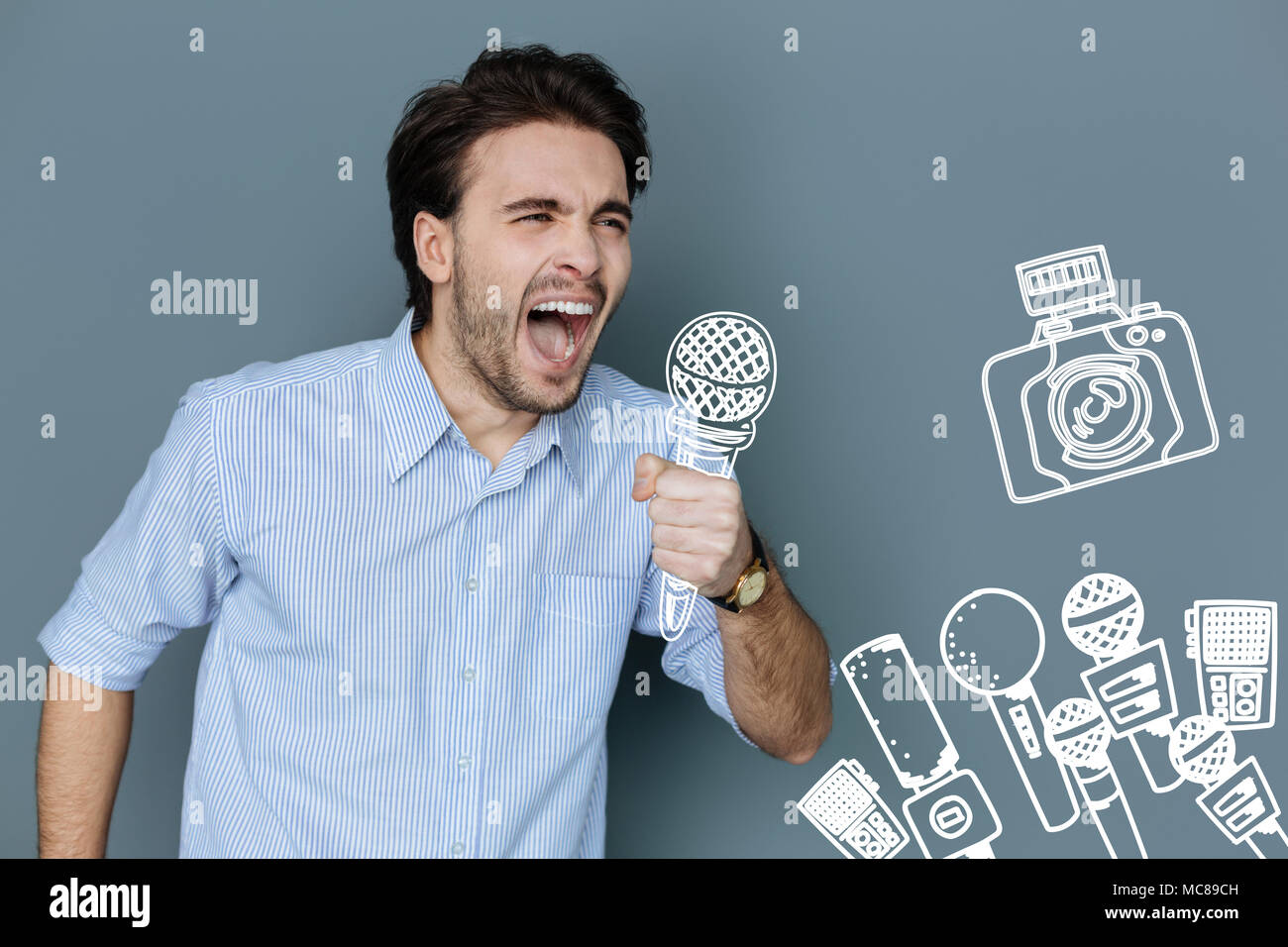 Enthusiastic singer holding a microphone and singing loudly - Stock Image