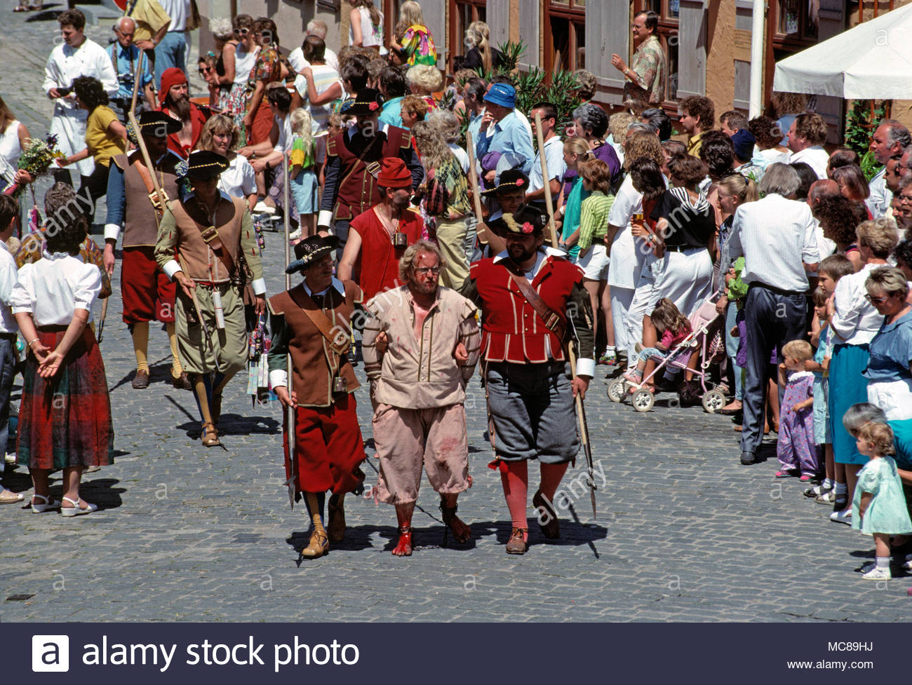 Germany. Dinkelsbuhl. Kinderzeche Dinkelsbühl - historic festival.  Street procession of male actors in period costume as prisoner escorted by guards. - Stock Image