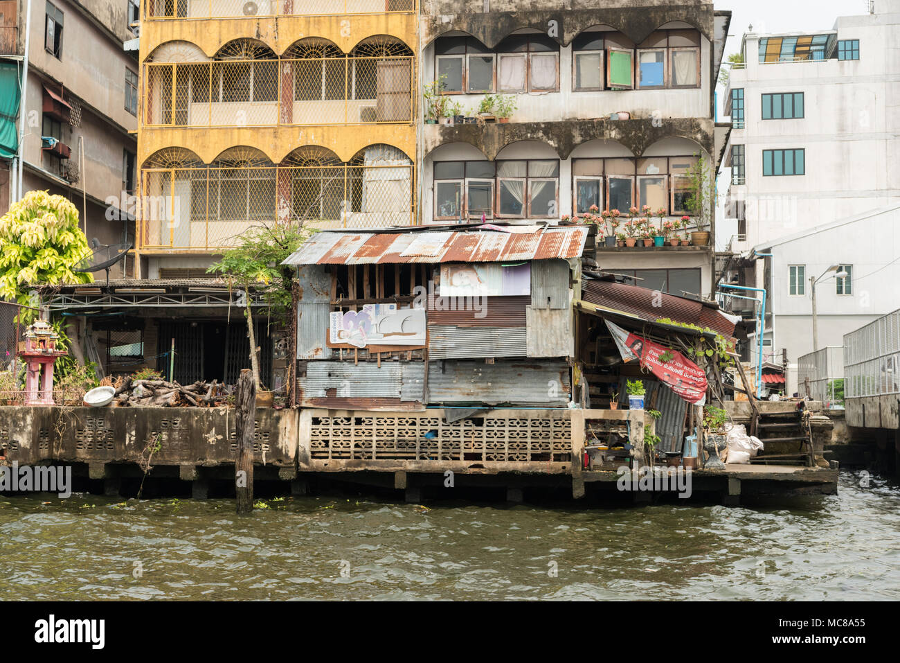 Rickety old buildings made from corrugated iron and wood alongside the Chao Phraya River in Bangkok, Thailand - Stock Image