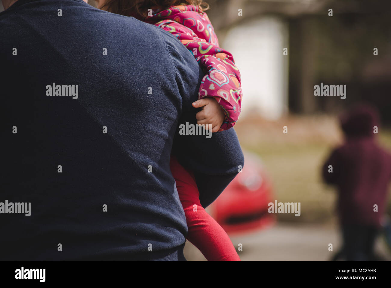 A child being held by her father. - Stock Image