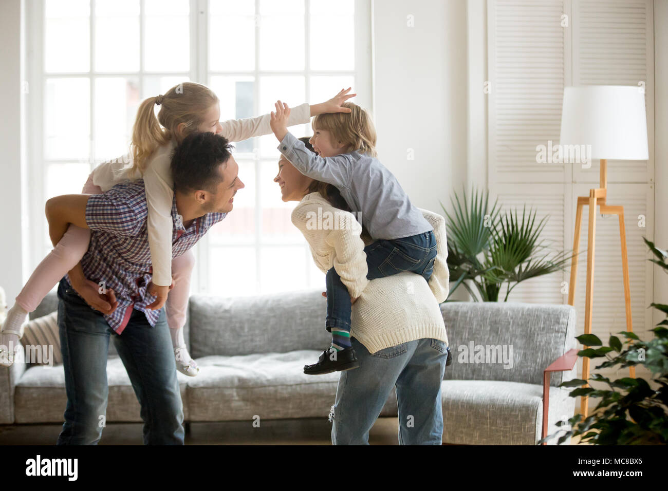 Happy young parents piggybacking son and daughter at home, smiling father and mother holding little kids on back spending time together, family having - Stock Image
