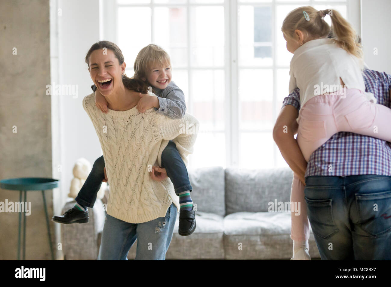 Happy mother laughing piggybacking little son playing with family at home, cheerful parents carrying kids on back having fun together, children boy an - Stock Image