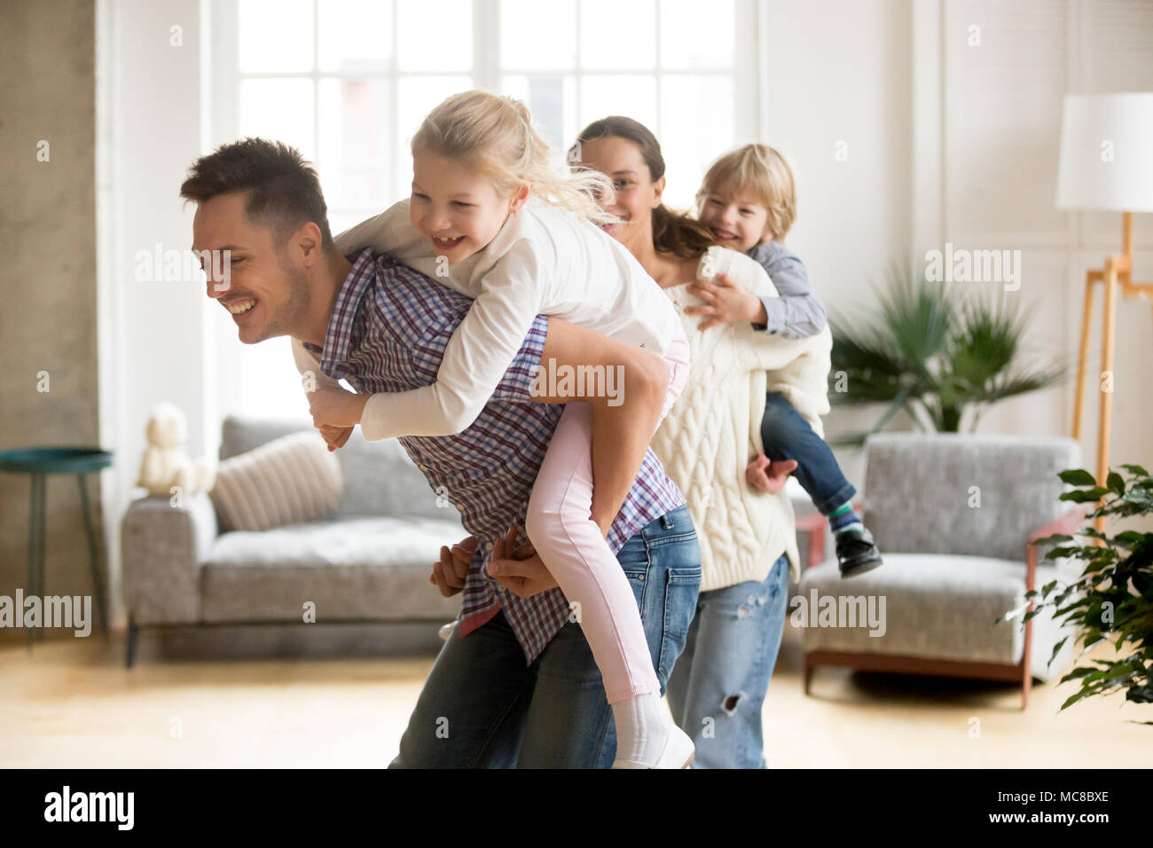 Happy loving dad piggybacking little daughter playing with family at home, smiling parents carrying kids on back, children boy and girl having fun tog Stock Photo