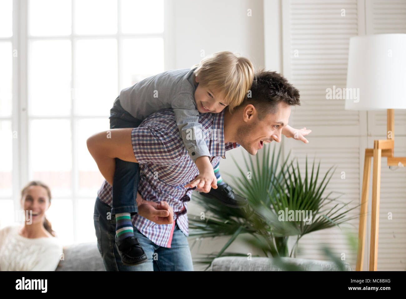 Happy dad holding little cute kid boy on back giving child piggyback ride having fun together at home, cheerful father playing with excited preschool  - Stock Image